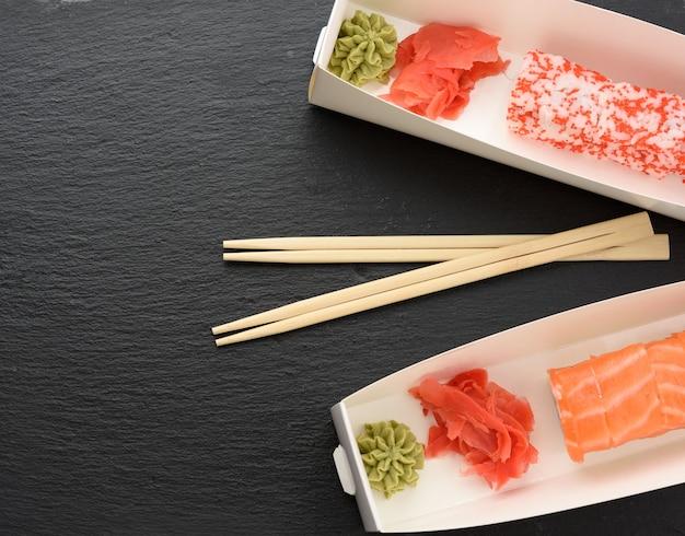 Sushi californiano con caviale tobiko rosso e fette di sushi di filadelfia con anguilla in una scatola bianca, consegna, vista dall'alto