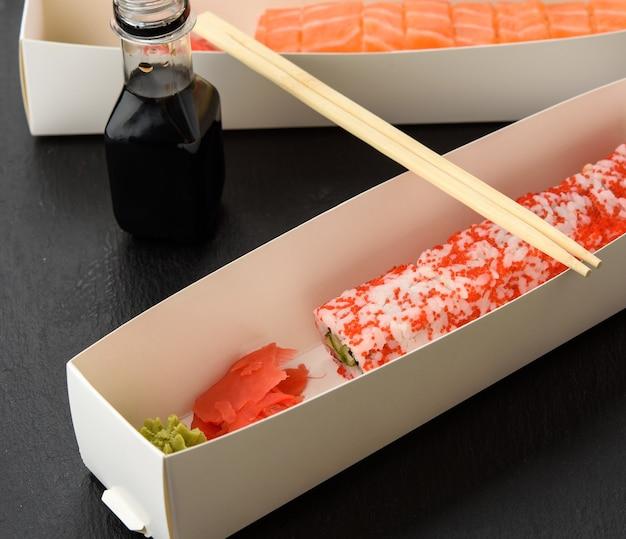 Sushi della california con caviale rosso di tobiko e fette di sushi di filadelfia con anguilla in una scatola bianca, consegna