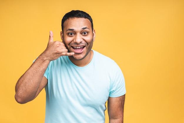 Chiamami segno. ritratto di un uomo di colore indiano afroamericano felice che parla sul telefono cellulare isolato sopra fondo giallo.