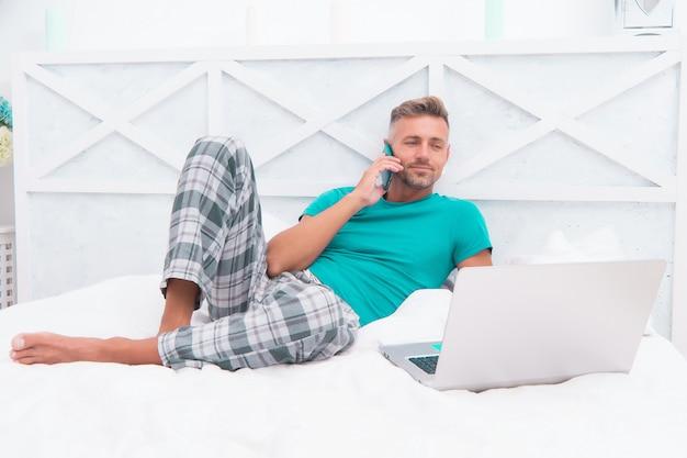 Chiama per ordinare cibo. l'uomo che naviga in internet lavora online. marketing digitale. accesso remoto. operaio maturo dei pigiami dell'uomo che si rilassa a casa servizi online. concetto di lavoro a distanza. social networks. mondo in linea.