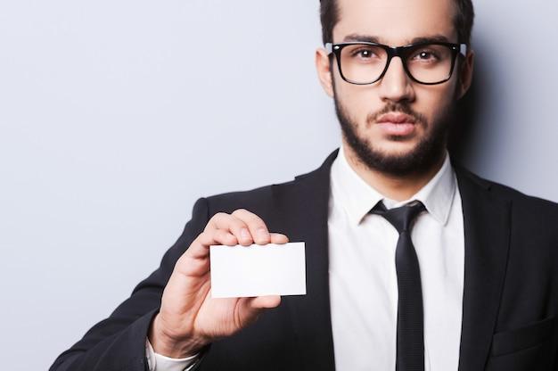Chiama questo numero! bel giovane in abiti da cerimonia che allunga un biglietto da visita mentre si trova su uno sfondo grigio