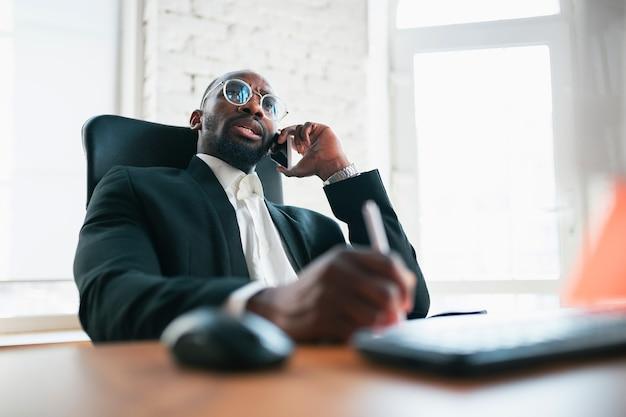 Chiamando, parlando al telefono. imprenditore afroamericano, uomo d'affari che lavora concentrato in ufficio. sembra serio, impegnato, indossa un abito classico. concetto di lavoro, finanza, affari, successo, leadership.