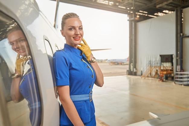 Calma e attraente assistente di volo che si tocca il mento con una mano nel guanto e sorride mentre si trova in un hangar