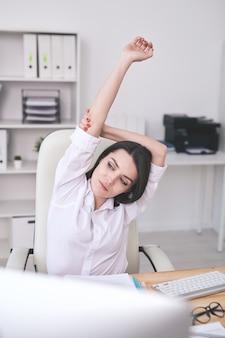 Calma attraente giovane imprenditrice in camicia bianca che si estende alla scrivania durante la pausa sul posto di lavoro