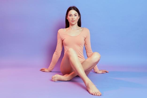 Calma bella donna con i capelli scuri, indossa un body beige, seduta sul pavimento e si appoggia sulle mani isolate sul muro blu con luce al neon rosa.