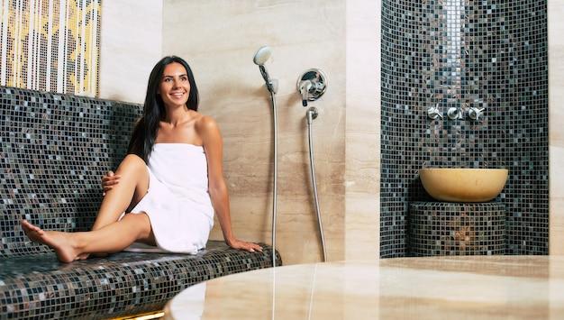 Calma bella giovane donna bruna con corpo snello e pelle sana sta riposando e prendere procedure termali nell'hammam o bagno turco