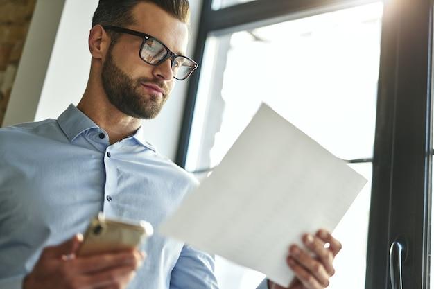Uomo d'affari calmo che lavora con i documenti in ufficio