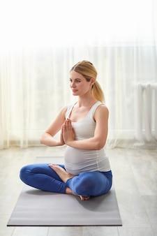 La donna incinta caucasica calma tiene le mani insieme meditando sul pavimento