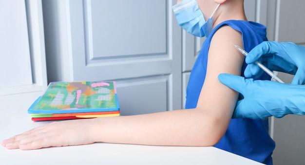 Un bambino calmo in maschera viene vaccinato e guarda un gioco educativo
