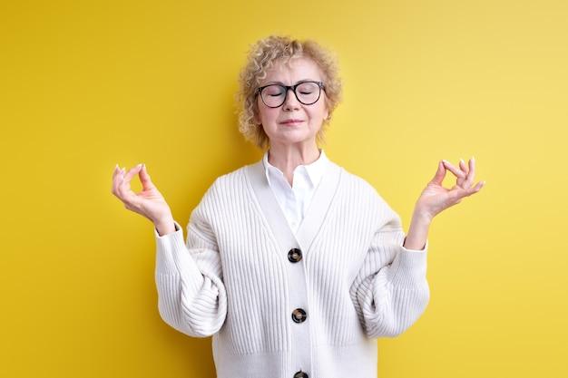 Calma donna invecchiata sicura in occhiali meditando isolato su giallo