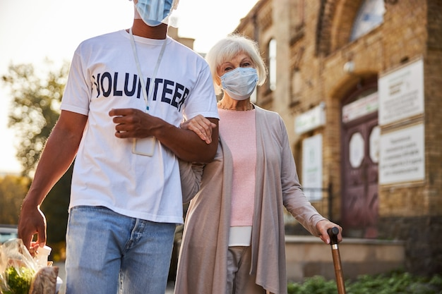 Calma signora anziana che indossa una maschera medica con in mano un bastone da passeggio mentre un volontario responsabile porta gli acquisti in un sacchetto di carta