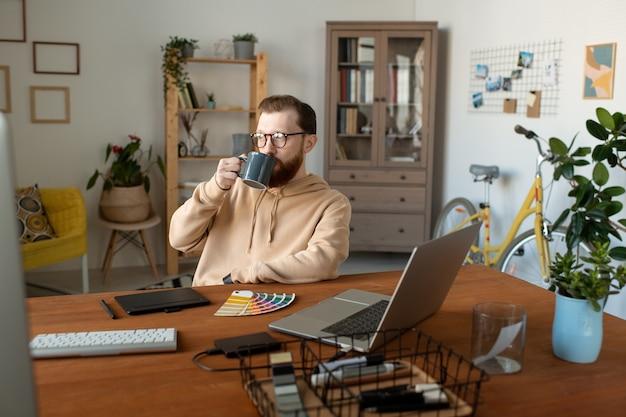 Calma bello barbuto designer seduto alla scrivania con i computer e bere il caffè in ufficio a casa