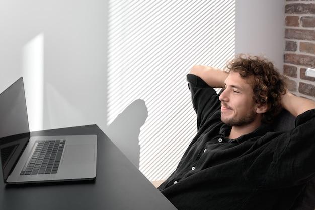 Calma giovane sorridente felice che riposa dopo il lavoro, formazione in ufficio a casa e allontanamento sociale in isolamento durante la pandemia di coronavirus