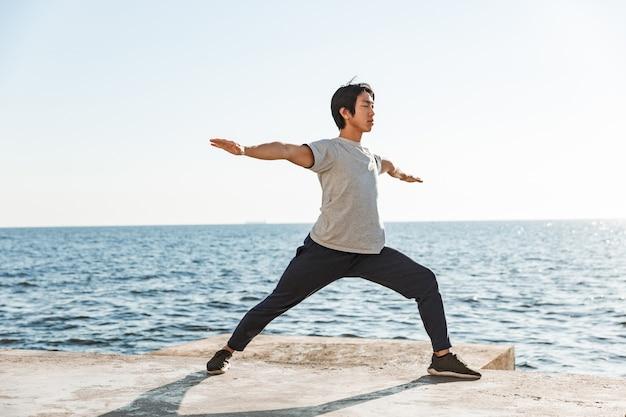 Uomo asiatico sano e calmo che fa esercizi di yoga in spiaggia, in equilibrio