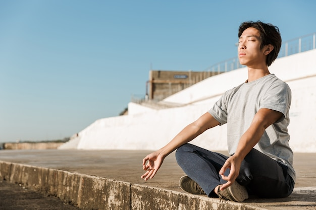 Uomo asiatico sano e calmo che fa esercizi di yoga in spiaggia, meditando