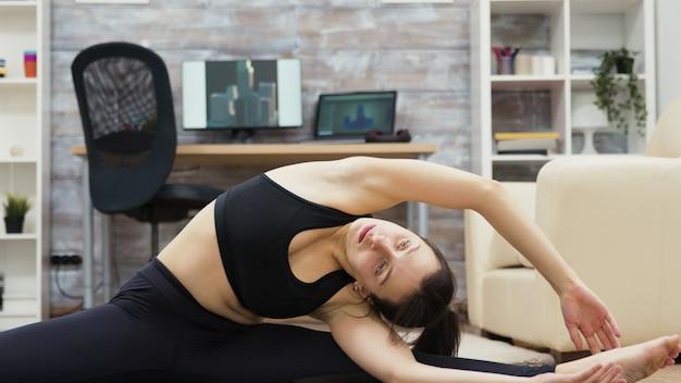 Calma e sana giovane donna che pratica yoga in soggiorno.