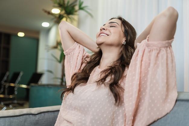 Calma donna latina che si rilassa su un divano morbido e confortevole che si gode senza stress sul divano