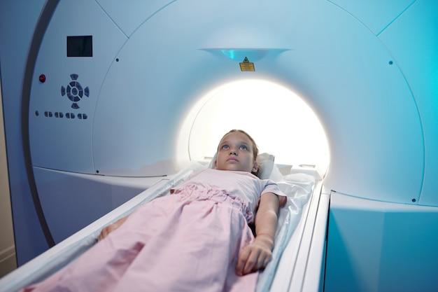 Piccolo paziente calmo che si sposta nella macchina per la risonanza magnetica per l'esame