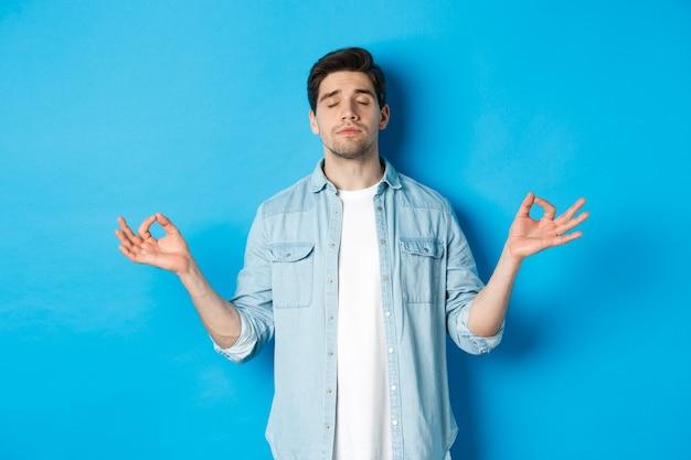 Uomo calmo con gli occhi chiusi, meditando, tenendosi per mano lateralmente e facendo esercizi di respirazione yoga, in piedi contro il muro blu