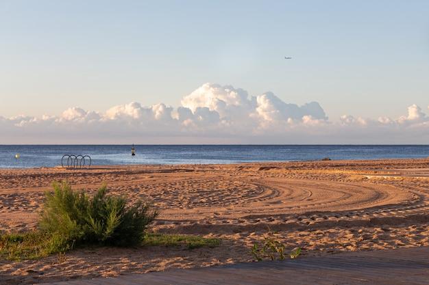 Mattina calma sulla spiaggia vuota con una gomma di auto stampe sulla sabbia, con mare e nuvole sullo sfondo