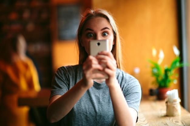 Calma pacifica bella giovane donna scattare una foto utilizzando la fotocamera anteriore dello smartphone in un bar o ristorante. tenere il dispositivo con entrambe le mani. da solo in camera