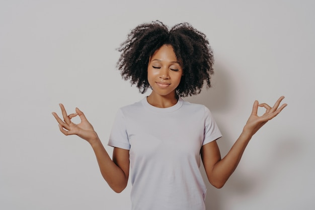 Calma e pacifica giovane donna di razza mista che tiene le mani nel gesto mudra e gli occhi chiusi