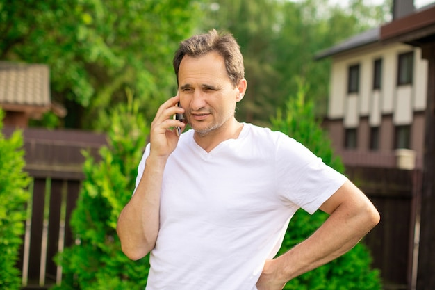 Ritratto calmo dell'uomo d'affari brunetta europeo maturo positivo che discute sullo smartphone durante le vacanze estive sulla natura verde vaga. il concetto di business per il controllo dei sentimenti