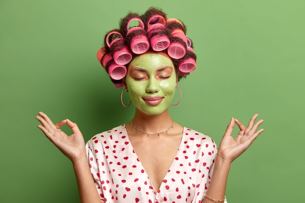 La donna calma e rilassata allarga le mani lateralmente nel gesto zen tiene gli occhi chiusi gode di un'atmosfera pacifica applica la maschera nutriente di bellezza per i rulli per la cura della pelle isolati sul muro verde
