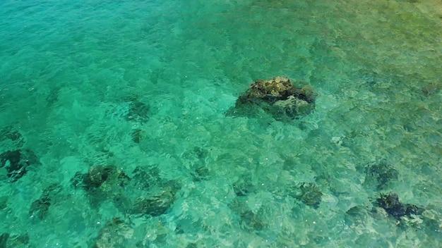 Acqua di mare calma vicino alle pietre. tranquilla acqua di mare blu e massi grigi in un luogo perfetto per lo snorkeling sull'isola di koh tao in una giornata di sole in thailandia. trama di sfondo naturale.
