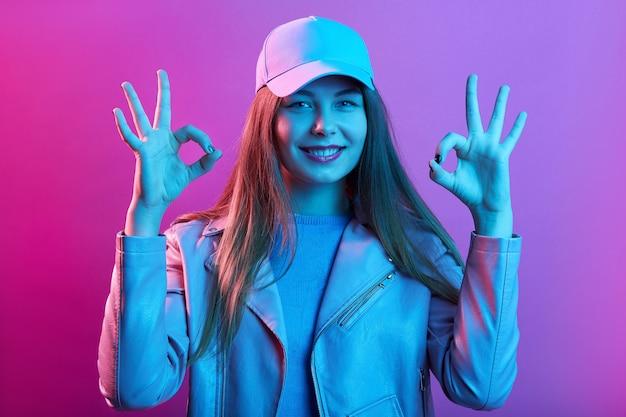 Calma sorridente giovane donna in posa al coperto, mostra il segno giusto con entrambe le mani, indossa abbigliamento casual, in piedi isolato su uno spazio rosa
