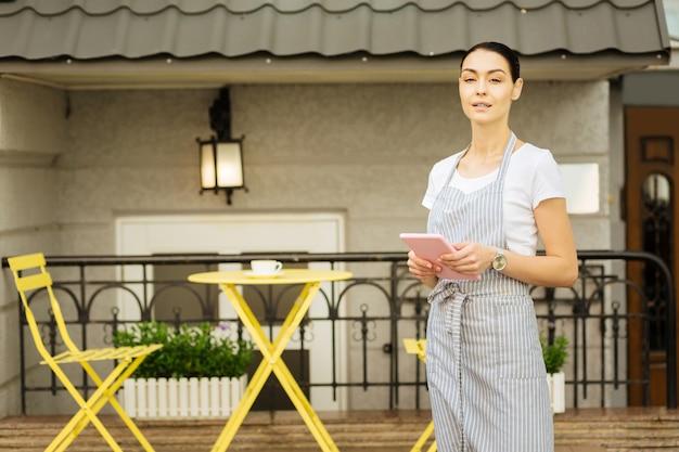 Calma cameriera. bella cameriera calma in piedi da sola su una terrazza estiva e in possesso di un dispositivo moderno
