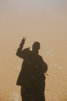 Acque calme sulla sabbia con l'ombra di un uomo