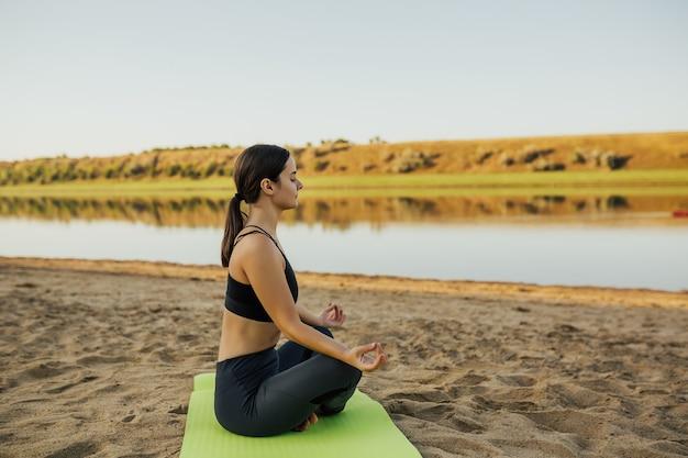 Calma donna meditando in lotus yoga sulla costa del fiume sulla spiaggia.