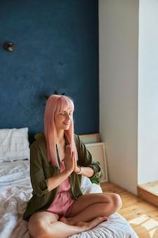 Una donna calma con lunghi capelli rosa medita tenendo la mano sin namaste su un letto grande