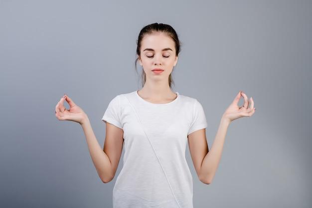 Giovane donna calma del brunette che si distende e che meditating isolata sopra grey