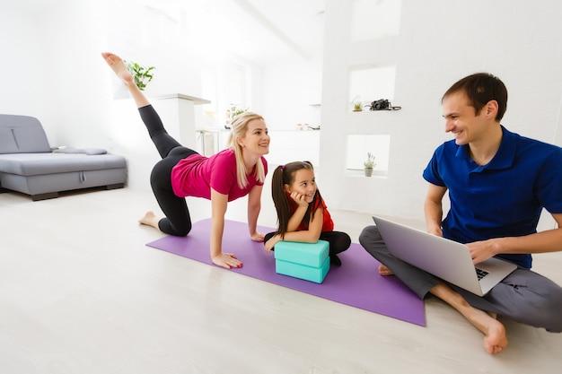 La giovane famiglia calma con la piccola figlia pratica lo yoga insieme, i genitori felici con la piccola bambina in età prescolare meditano alleviare le emozioni negative durante il fine settimana a casa