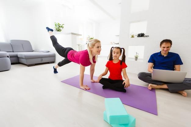 La giovane famiglia calma con la piccola figlia pratica insieme l'yoga, i genitori felici con la piccola ragazza del bambino in età prescolare durante il fine settimana a casa