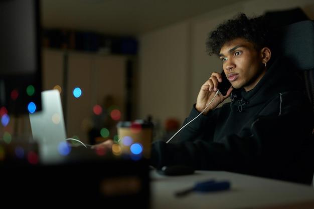 Calmo giovane bel ragazzo che parla al telefono mentre lavora al laptop seduto a casa da solo fino a tardi