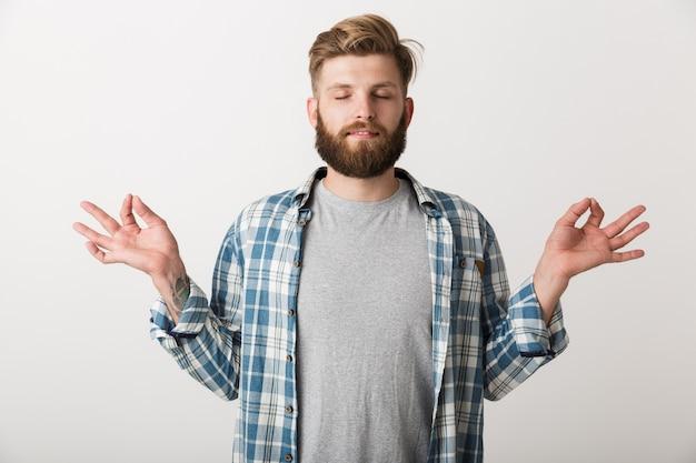 Calmo giovane uomo vestito con una camicia a quadri in piedi isolato, meditando con gli occhi chiusi