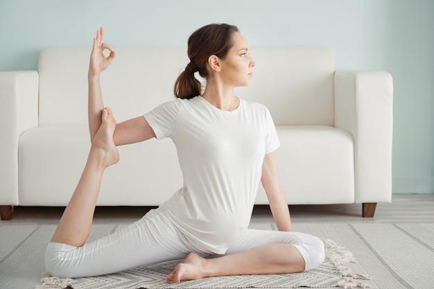 Calma giovane donna incinta bruna fa ardha matsyendrasana praticando la posizione yoga sul pavimento vicino al divano di casa close-up