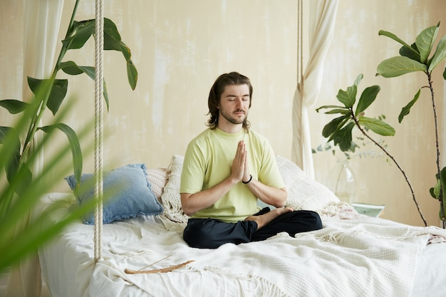 Uomo calmo in yoga sana sul letto e namaste, meditatore pacifico concentrato a casa la mattina