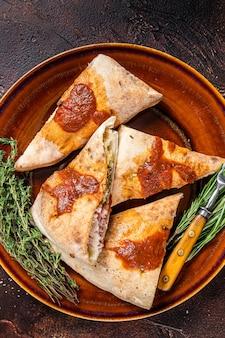 Pezzi di pizza calzone su piatto rustico con salsa di pomodoro ed erbe aromatiche. sfondo scuro. vista dall'alto.