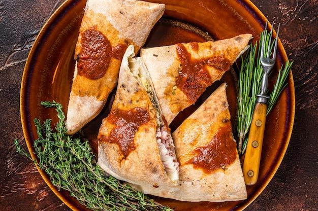 Pezzi di pizza calzone su piatto rustico con salsa di pomodoro ed erbe aromatiche