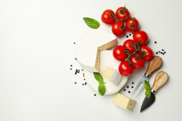 Formaggio camembert, basilico, pomodoro, coltelli e pepe su sfondo bianco, spazio per il testo