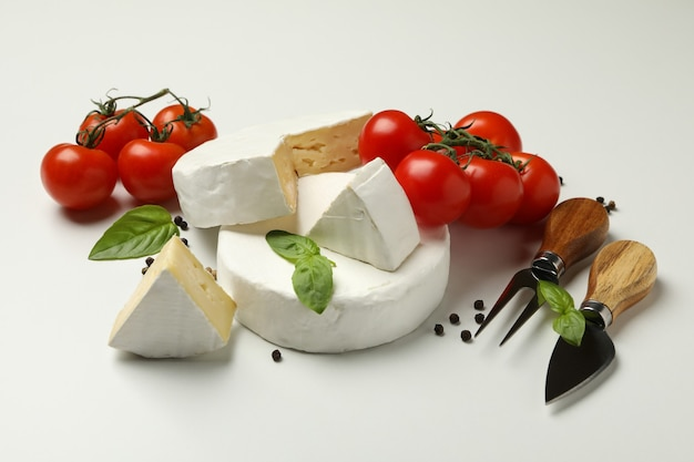Formaggio camembert, basilico, pomodoro, coltelli e pepe su sfondo bianco
