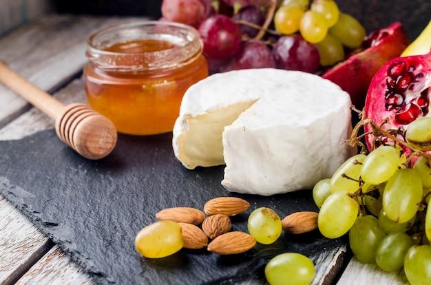 Primo piano del formaggio camembert con miele, noci, vite. piatto di formaggi squisito, cibo da vino. camembert, bree. formaggio francese a pasta molle. cibo italiano. latticini.