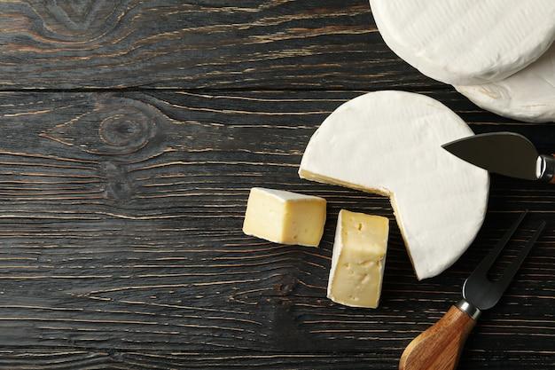 Formaggio camembert e coltelli su sfondo di legno, spazio per il testo