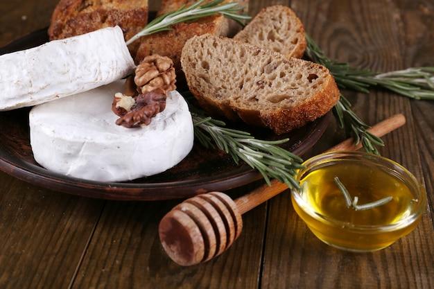 Formaggio camembert su piatto, miele, noci e pane su fondo di legno