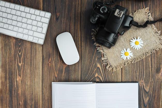 Fotocamera, tastiera del computer e fiori di campo su legno scuro.