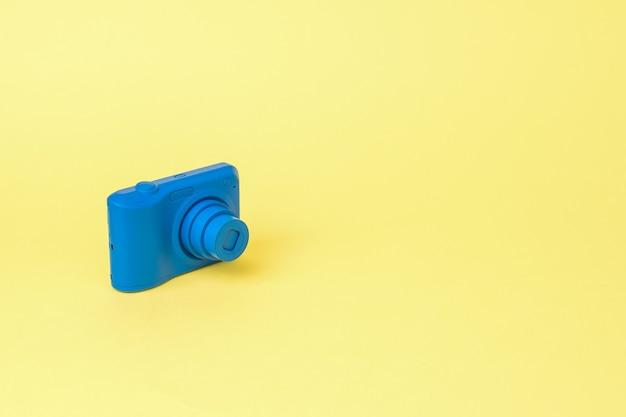 La fotocamera è di un colore blu brillante su sfondo giallo. attrezzatura elegante per riprese di foto e video.